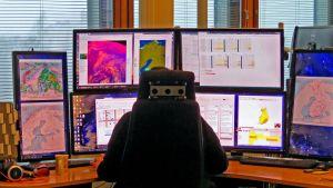 Mies istuu selin monitoririvistön edessä. Monitoreissa karttoja, joissa sään ennustamiseen käytettyjä tietoja karttoina.