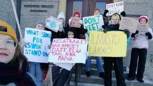 Nuoria Joensuun kaupungintalon portailla banderollien kanssa.