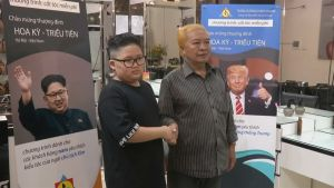 Kuvassa kättelevät poika, jonka hiukset on leikattu Kim Jong-unin tyylillä ja mies, jonka hiukset on leikattu Donald Trumpin tyyliseksi.