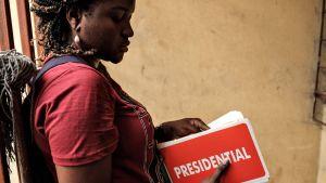 Naisella on kädessään presidentinvaaleista tiedottavia punaisia tarralappuja.