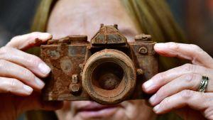 Nainen pitelee käsissään kameran näköistä suklaaluomusta Brysselin suklaamessuilla 21. helmikuuta.