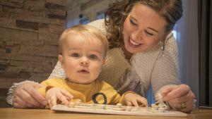 Äiti ja taapero leikkivät palapelillä pöydän ääressä.