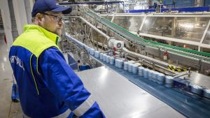 Lonkerotölkkejä tehtaan hihnalla, työntekijä valvoo.