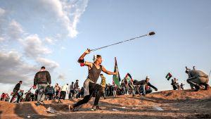Nuori palestiinalaismies heiluttaa oikeassa kädessään pitkää ritsaa, jossa on ammuksena kiviä.