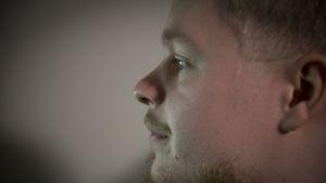Mies tuijottaa tietokoneen näyttöä, sivuprofiili
