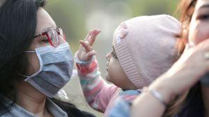 Intialaisäiti osoitti mieltään ilmansaasteita vastaan Kolkatassa viime joulukuussa.