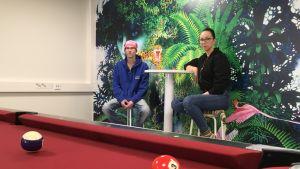 Nuoriso-ohjaajat Tuomo Mikkonen ja Jonna Härkönen istuvat uudessa nuorisotilassa. Etualalla on biljardipöytä.