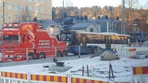 Moottoritilan ympäriltä palanutta bussia hinataan Tampereen keskustassa.