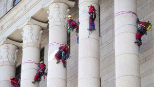 Ympäristöjärjestö Greenpeacen haalareihin pukeutuneita ihmisiä eduskunnan pylväissä.