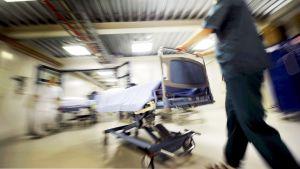 Sairaanhoitaja työntää sairaalasänkyä käytävällä.