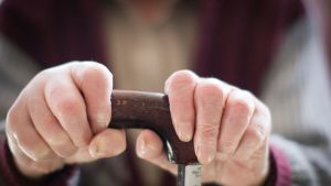Vanha nainen pitää kävelykepistä molemmin käsin