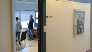 Kaksi ihmistä keskustelee työhuoneessa.