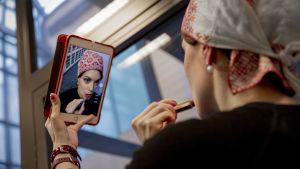 Nainen kansallispuvun myssy päässä peilaa itseään puhelimen näytöltä ja laittaa huulipunaa