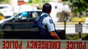 Kuvassa aseistettu poliisi poliisin eristysnauhan takana.