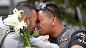 Kaksi miestä kukka kädessä.