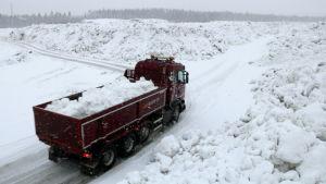 Kuorma-auto kuljettaa lunta.