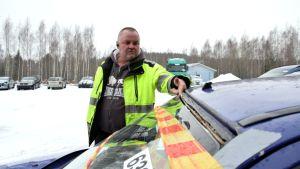 Varikonhoitaja Olli Laine tutkii auton irti olevaa tuulilasia.
