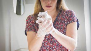 Nainen hinkkaa käsiään saippualla puhtaaksi.