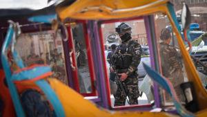 Afganistalainen sotilas tarkkailee pommi-iskualuetta.