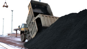 Maansiirtoauto tyhjentää kivihiililastia satamalaiturille
