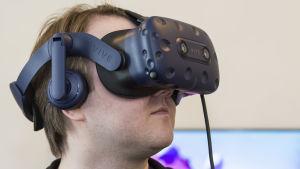 Miehellä on päässään VR-lasit.
