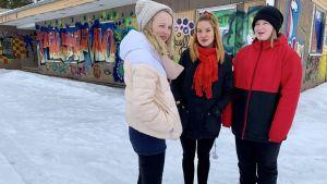 Pihla Puheliinen, nuoriso-ohjaaja Jenna Heikkinen ja Tiia Kvist seisovat Paltamossa nuorten taiteileman graffitin edessä.