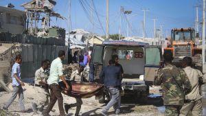 Iskun uhria kennetaan ambulanssiin Mogadishussa.