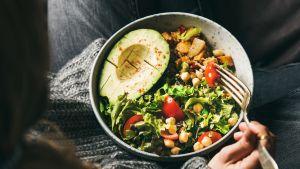 nainen syö kasvisruokaa