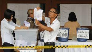 Kuvassa ääntenlaskentaa Thaimaan Chiang Maissa. Kuvassa keskellä silmälasipäinen miespuolinen vaalivirkailija pitää käsissään paperia.