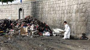 Jemeniläispoika työnsi roskia kottikärryssä Sanaassa viime viikolla. Roskia kasattiin ja desinfioitiin taistelussa koleraepidemiaa vastaan.