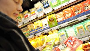 Nuori mies vertailee eri juustoja ruokakaupassa.