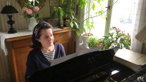 Merja Innilä soittaa pianoa ikkunan edessä.