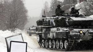 Panssarivaunut ajavat ruotsalaisella kylänraitilla.