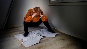 Nainen istuu lattialla ja katsoo talon pohjapiirrustusta.