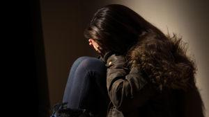 Nuori tyttö istuu lattialla peittäen kasvonsa käsillään murheellisena.