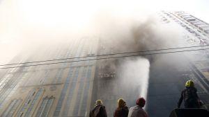 Palomiehet ruiskuttavat vettä kohti palavan kerrostalon julkisivua.