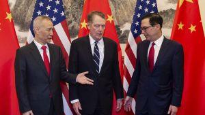 Kolmikko seisoo Kiinan ja Yhdysvaltain lippujen edessä. Kiinan varapääministeri Liu He keskusteli Yhdysvaltain kauppaedustajan Robert Lighthizerin ja valtiovarainministeri Steven Mnuchinin kanssa Pekingissä.