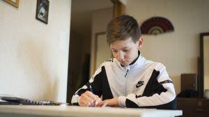 Samu Hautala piirtää pöydän ääressä.