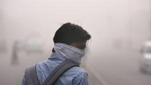 Mies on käärinyt kasvonsa kankaaseen ja kävelee savusumussa.