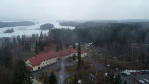 Karkun evankelinen opisto Sastamalassa. Rakennuksen taustalla hakattavaksi suunniteltua metsää ja vesistöä.