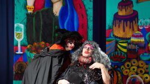 Mustissa vaatteissa nainen teatterimeikissä ja mies meikissä ja harmaassa isossa peruukissa.