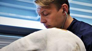 Eläinlääkäri Jaakko Väyrynen kuuntelee koiran sydänääniä Oulun kaupungin eläinklinikalla.