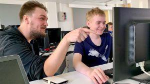 Oppilas ja opettaja katsovat tietokoneen näyttöä koulun luokassa.