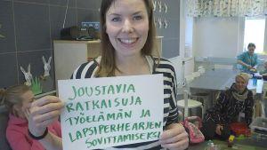 Jenni Lehtilä näyttää paperille kirjoittamaansa viestiä päättäjille.