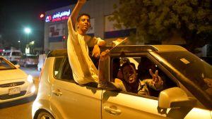 Nuoret juhlivat Khartumin kaduilla perjantaina. Kuvassa nuori mies näyttää voitonmerkkiä auton ikkunasta.