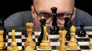Mies katsoo shakkilautaa shakkinappuloiden takaa.