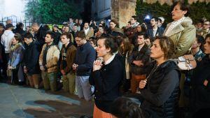 Ihmiset rukoilivat jalkakäytävällä Notre Damen lähistöllä 15. huhtikuuta.