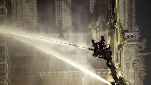 Palomies nostolava-auton korissa sammuttamassa Notre Damen paloa.