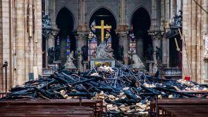 Kuva Notre Damen katedraalin sisältä palon jälkeen. Ristin ja penkkien välissä on palossa syntynyttä rojua.