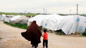 Isis-taistelijaksi epäillyn miehen vaimo käveli maaliskuussa poikansa kanssa Rojin pakolaisleirillä Koillis-Syyriassa.